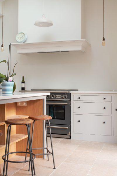 White oak shaker style kitchen with island breakfast bar, range cooker, and cornice over extractor hood
