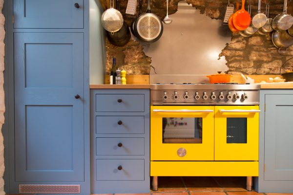 Blue shaker style kitchen with bright yellow cooker