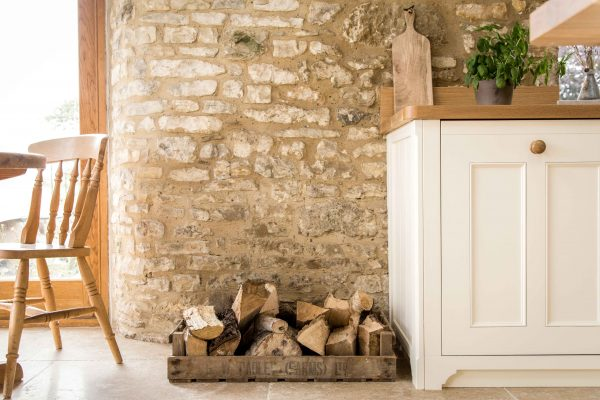 Barn conversion house in an old country style, exposed brick wall with farmhouse sink, with oak worktops, country style cabinetry.