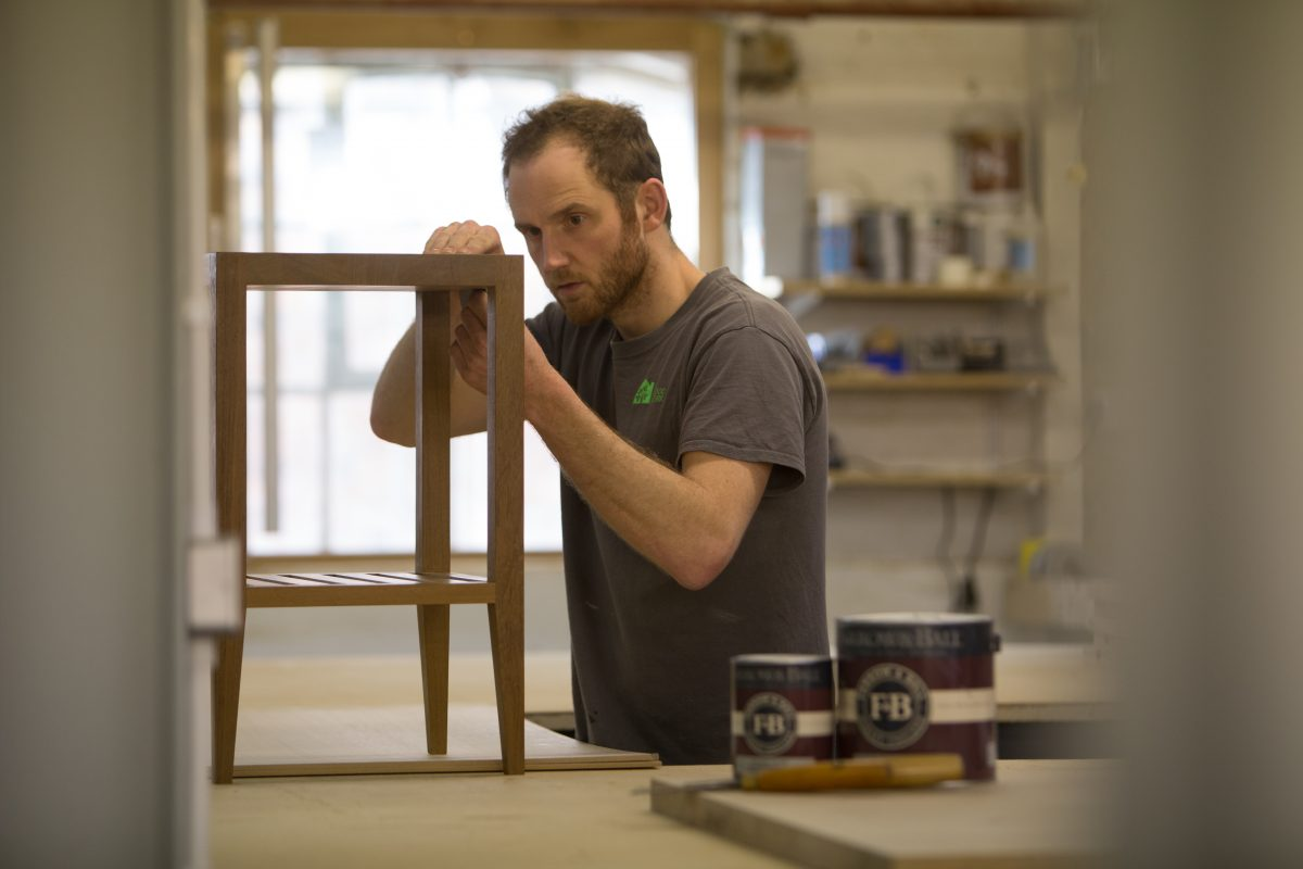 Charlie inspecting the craftsmanship on a bespoke side table.