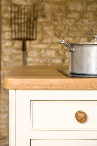 Detail of oak island worktop with beading and moulding and varnished knob