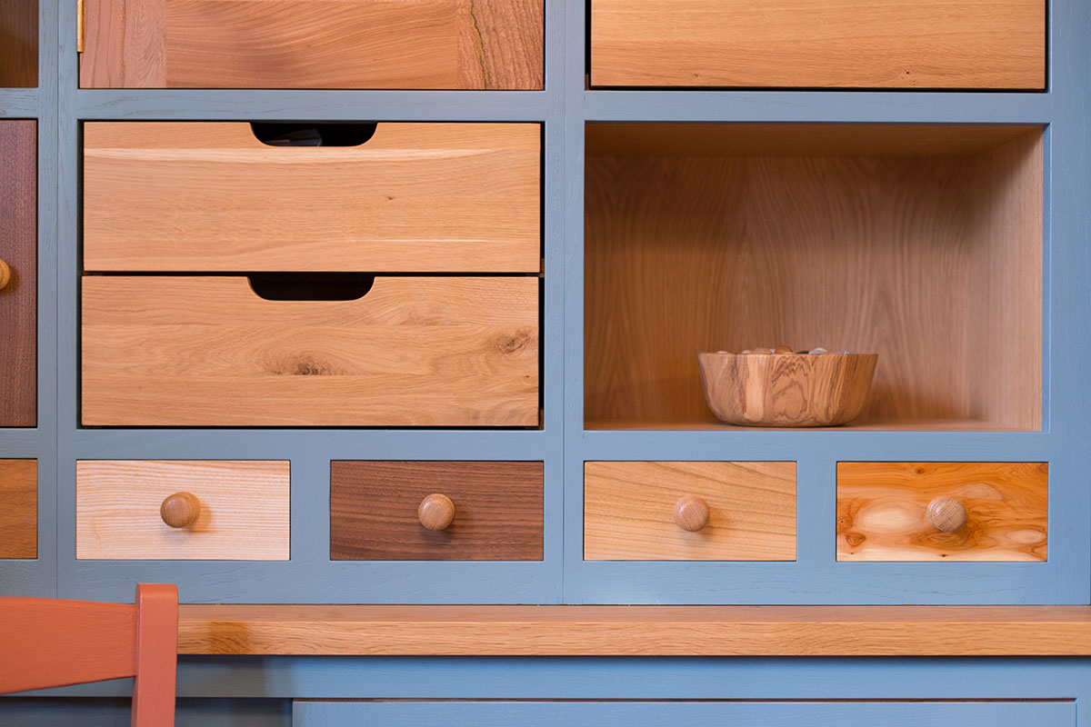 Detail of cabinet with small wooden drawers in ash, walnut, beech, and yew