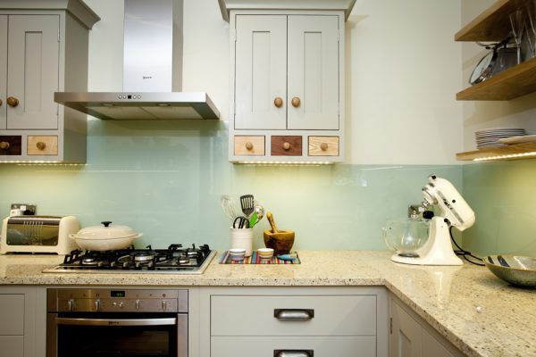 Shaker style kitchen with sandstone worktop and LED lights