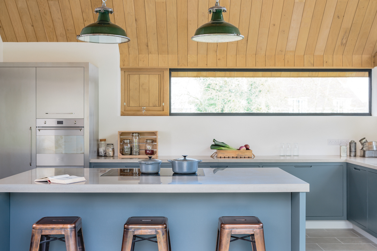Our Showroom shaker kitchen showing the centre island with concrete worktop with open shelving. Copper tap and oversized copper  Davey spun pendant lighting.