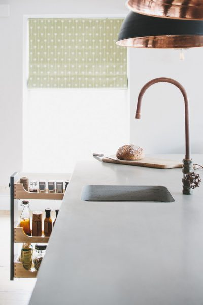 Concrete worktop with under mount sink and copper tap with open larder drawer