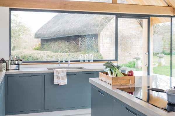 View of flat panel oak kitchen and island with large windows overlooking garden