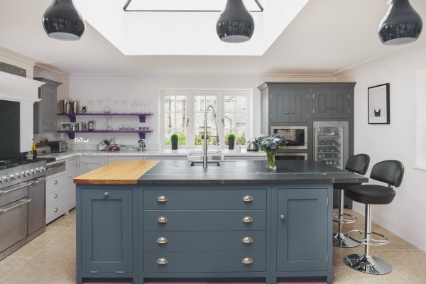 Contemporary shaker style well illuminated kitchen with large island and breakfast far