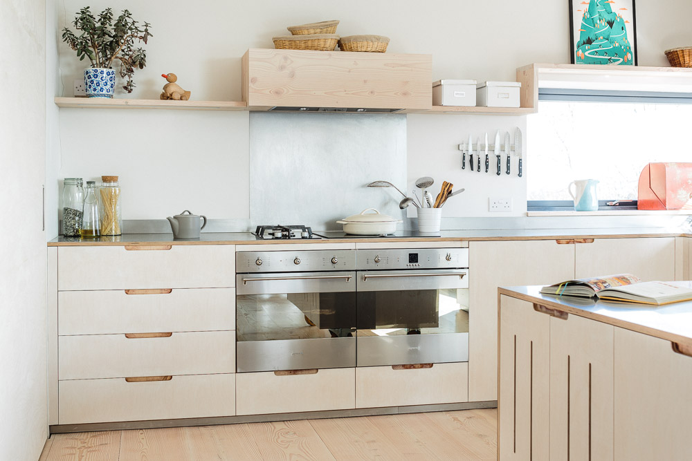 A contemporary plywood kitchen with stainless steel worktops and cladded floating island.