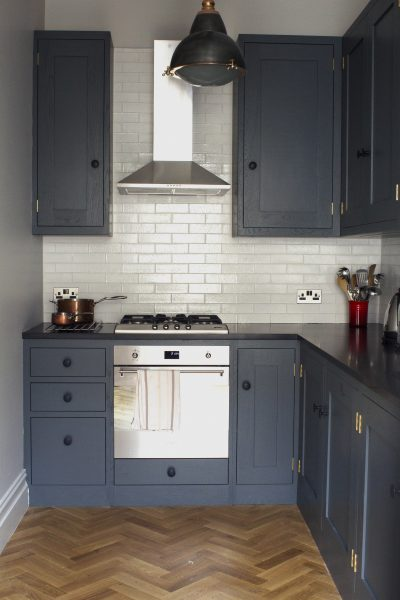 Oak shaker kitchen painted in down pipe with white metro tiles and parquet flooring