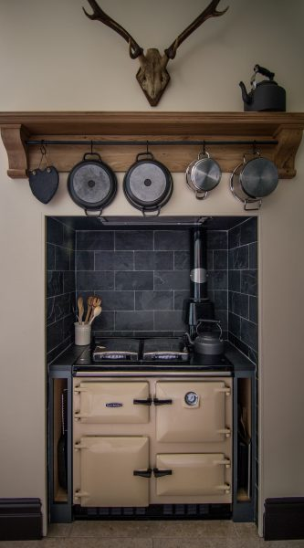 Cream Rayburn cooker with slate wall tiles and tray slots on the side and oak mantlepiece