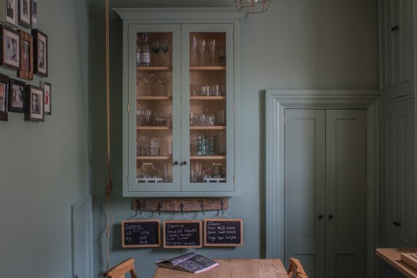 Glazed wall cabinet painted in Farrow & Ball Chappell Green