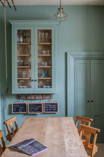 Glazed wall cabinet painted in Farrow & Ball Chappell Green with pine table and chapel chairs