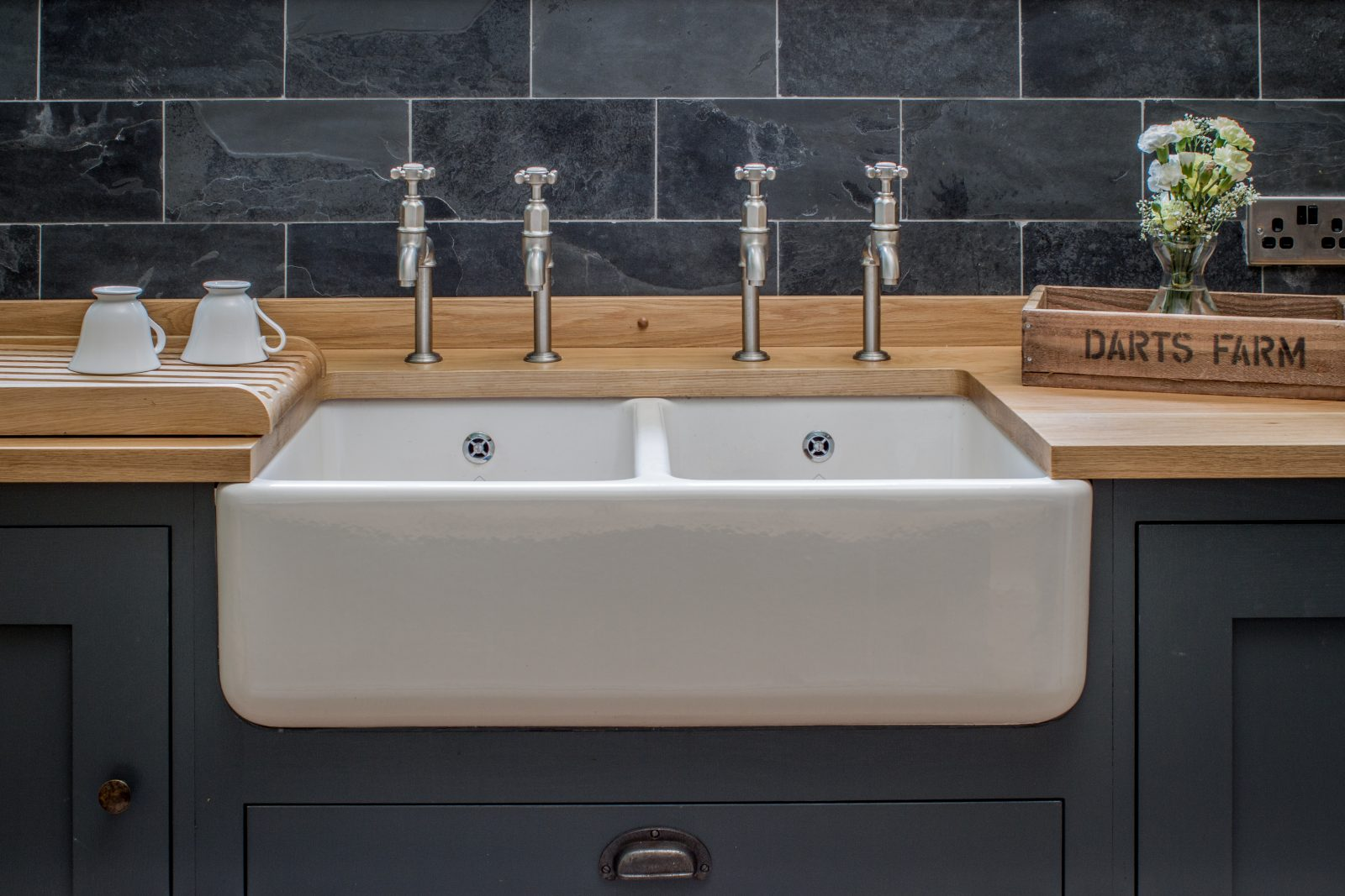 Belfast farmhouse sink with double bibcock taps and slate wall tiles