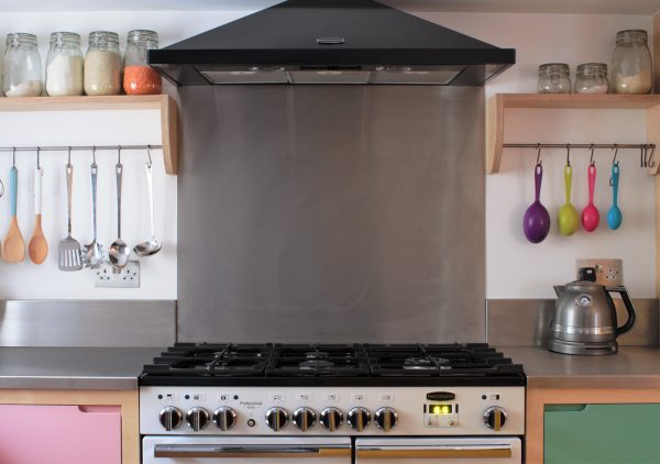 A white range cooker with stainless steel splashback in a colourful flat panelled plywood kitchen