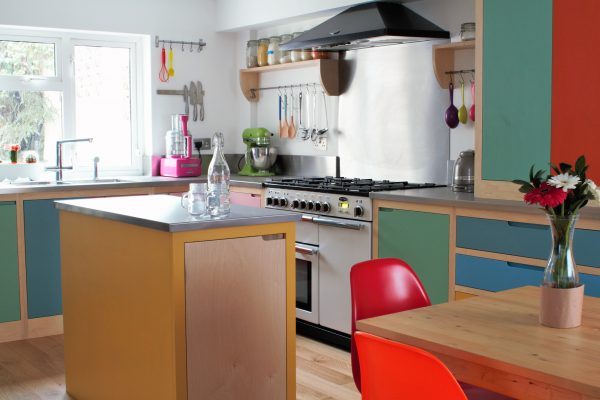 Colourful Farrow & Ball painted flat panelled plywood kitchen with centre island and colourful kitchen accessories