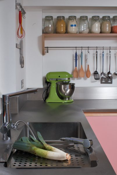 Colourful flat panelled plywood kitchen with inbuilt sink, stainless steel worktop, and exposed oak shelving