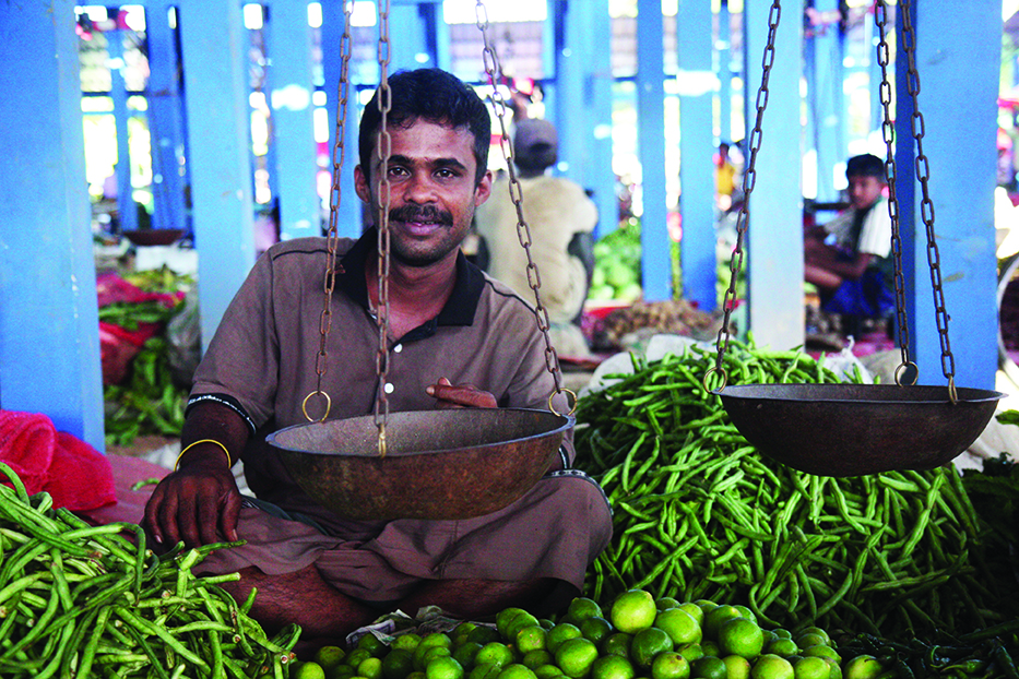 The Locals Cookbook - Man in local market with limes