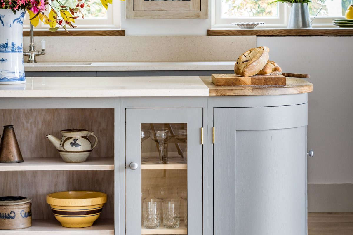 Oak shaker kitchen with open shelving and glazed cabinets set within a curved kitchen island