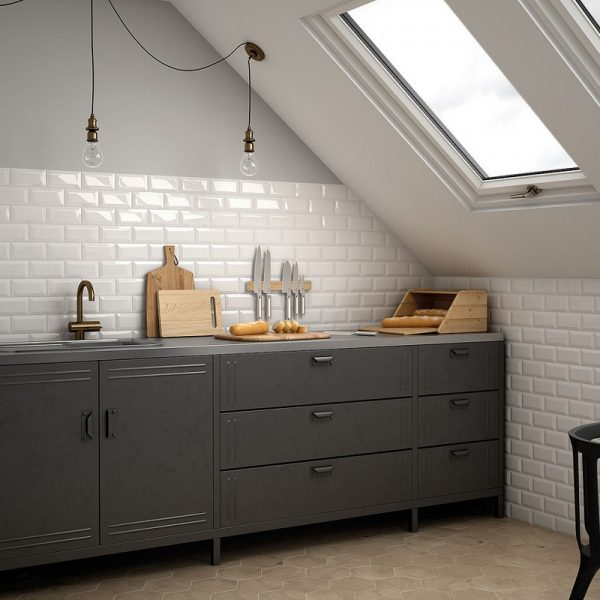 Dark grey industrial freestanding kitchen with plain white bevel edged metro tile spalshback. Grey wall and industrial bare bulb lighting
