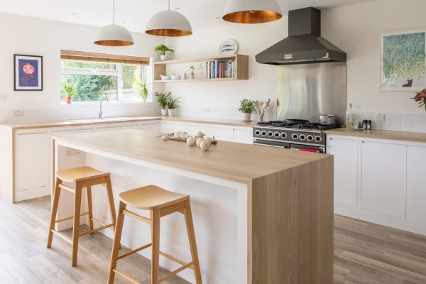 View of flat panel white minimalist kitchen with island, oak worktops and copper pendant lights