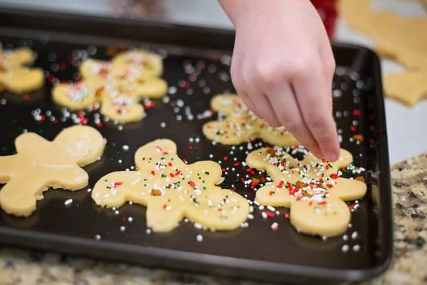 Child putting sprinkles on Christmas cookies on a baking tray