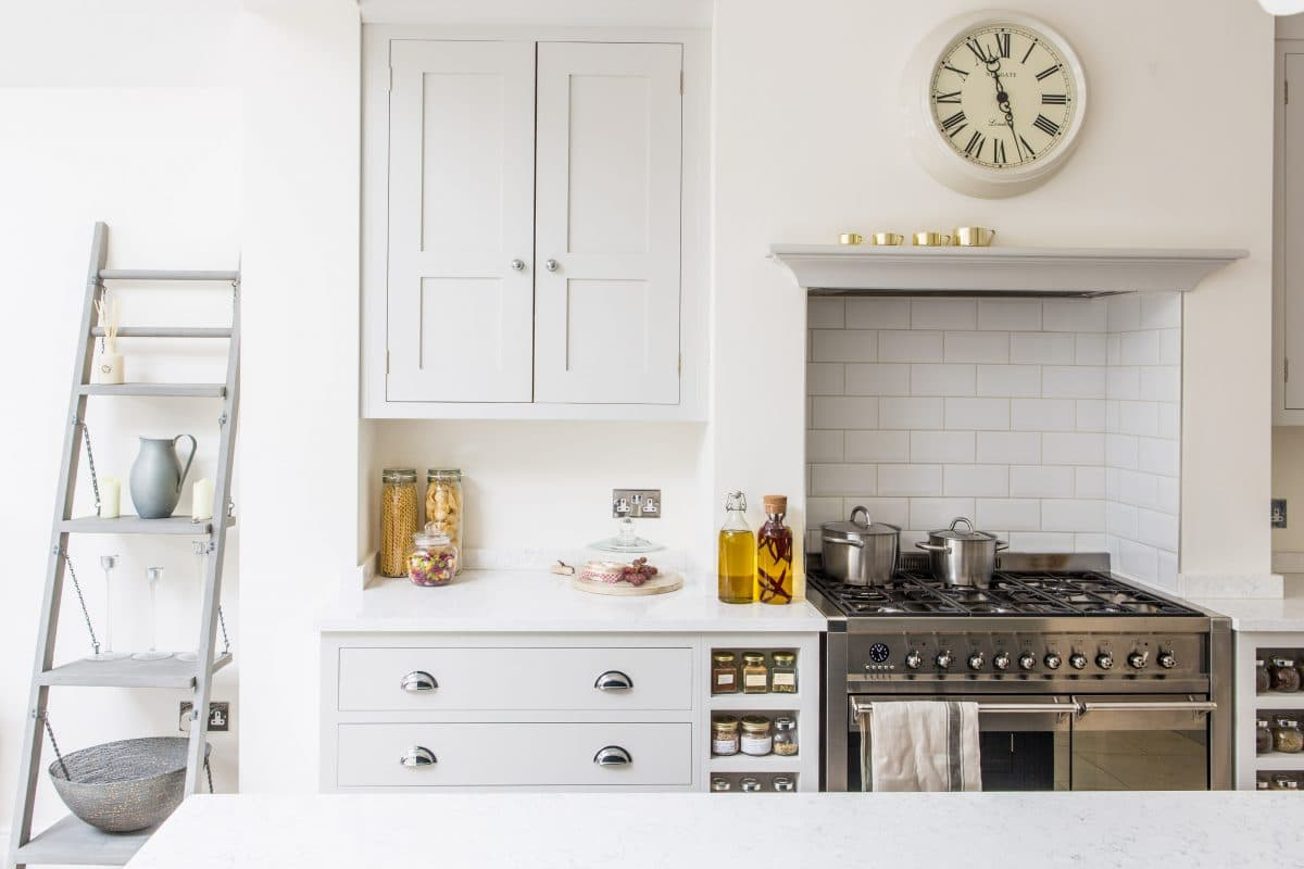 Oak shaker style cabinetry painted in Farrow & Ball Ammonite with built in spice racks next to the range cooker and decorative ladder