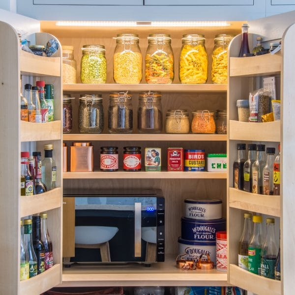 Open larder pantry cupboard with spice racks on both doors filled with mason jars and condiments with LED lights that are switched on