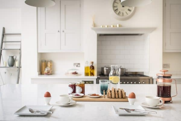 Breakfast spread with bread, jam, coffee and eggs on an island Bianco Fantasia worktop