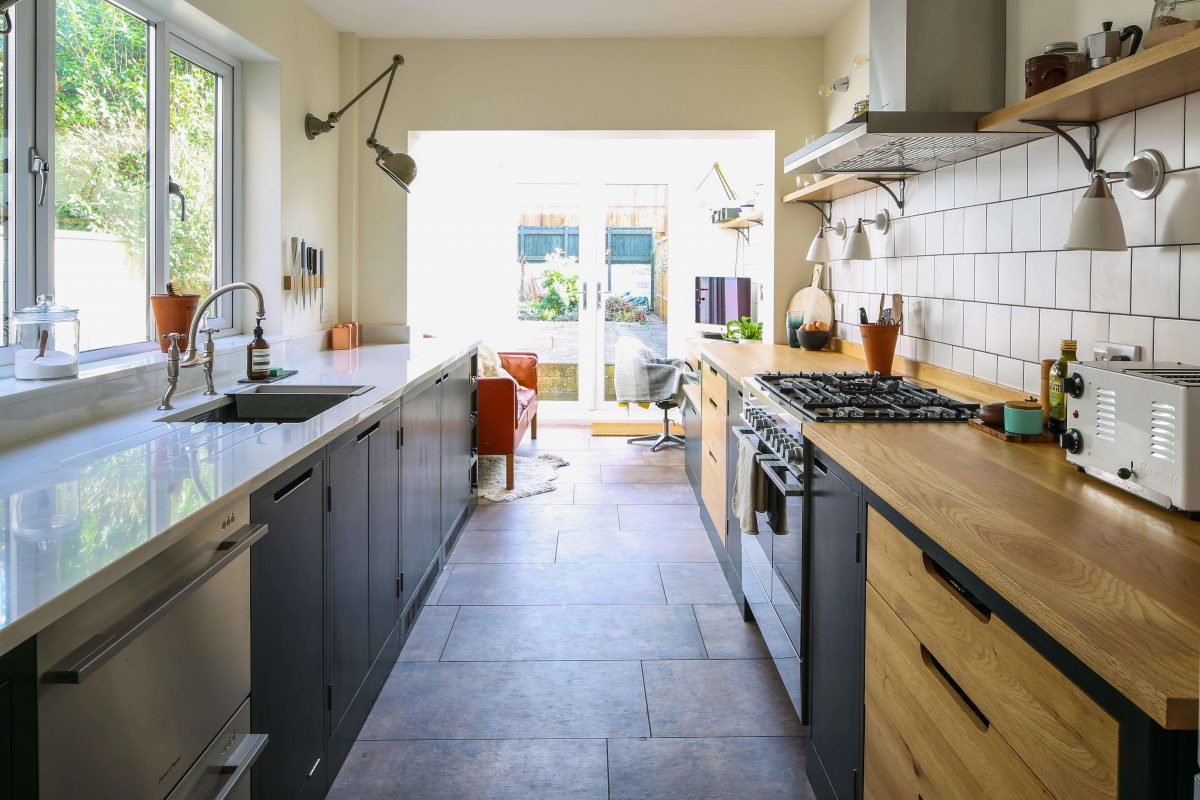 View of oak and ply flat panel galley kitchen with oak and engineered quartz worktops