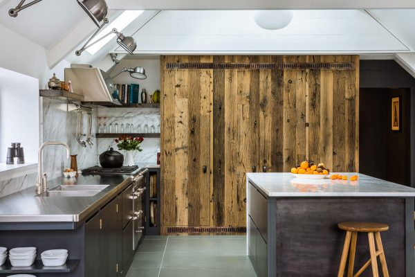 View of dark kitchen with an island and larder clad with boxcar oak.