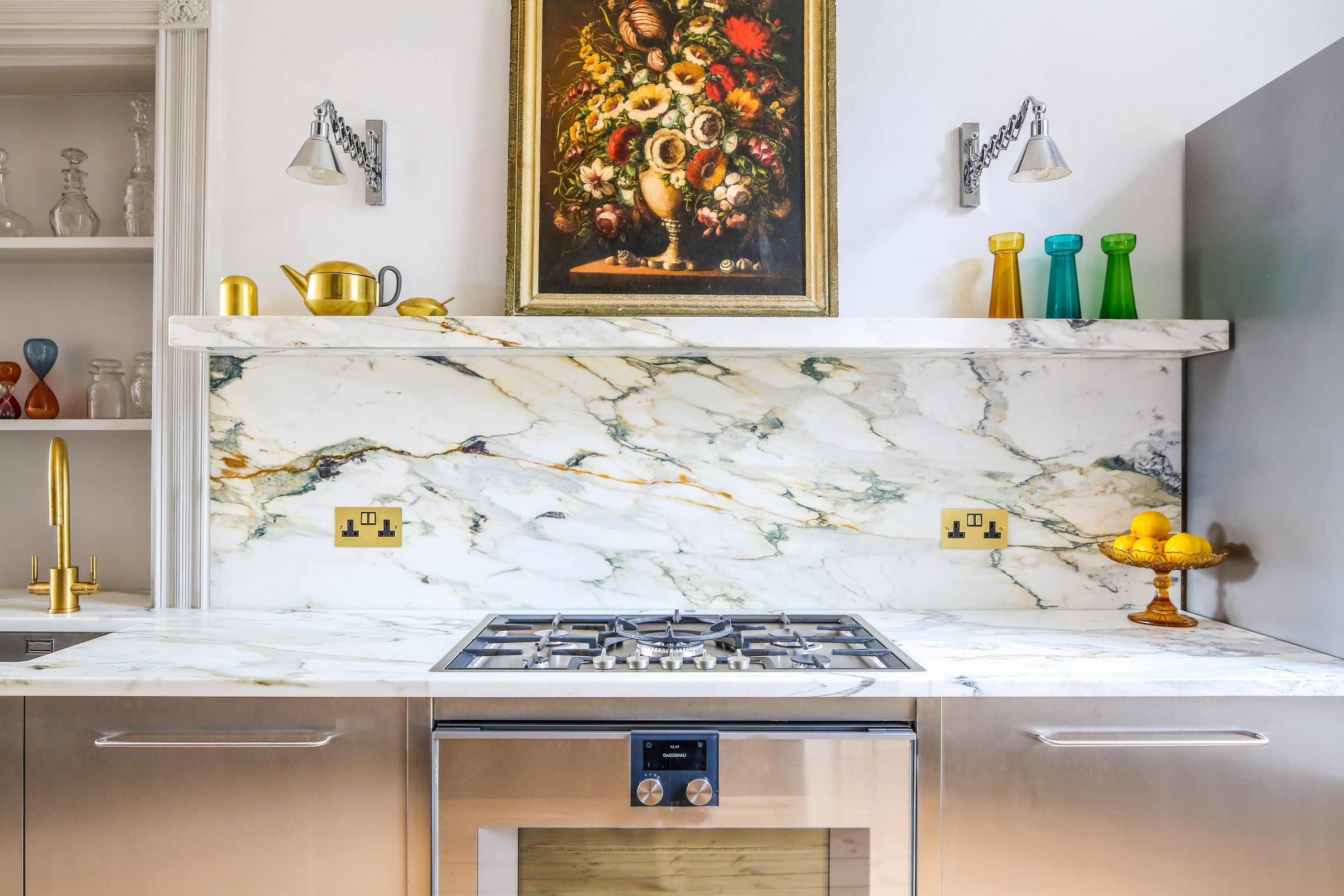 View of kitchen cabinets wrapped in Stainless Steel with a marble worktop with gas hob and sink.