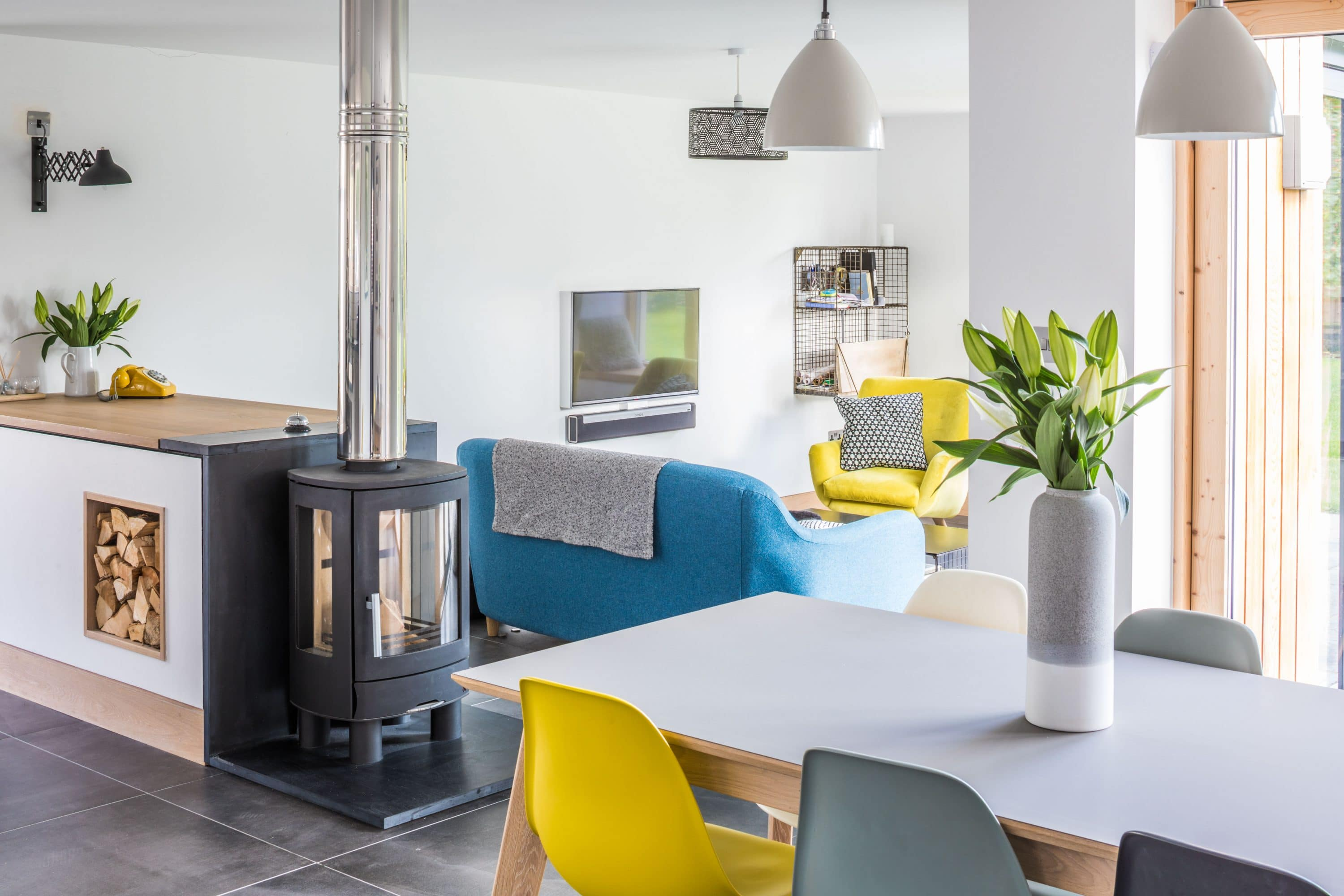 View of dining room with log burning stove in the foreground and retro furniture