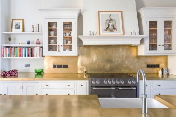 View of White shaker kitchen cabinets and island with a brass worktop and splashback