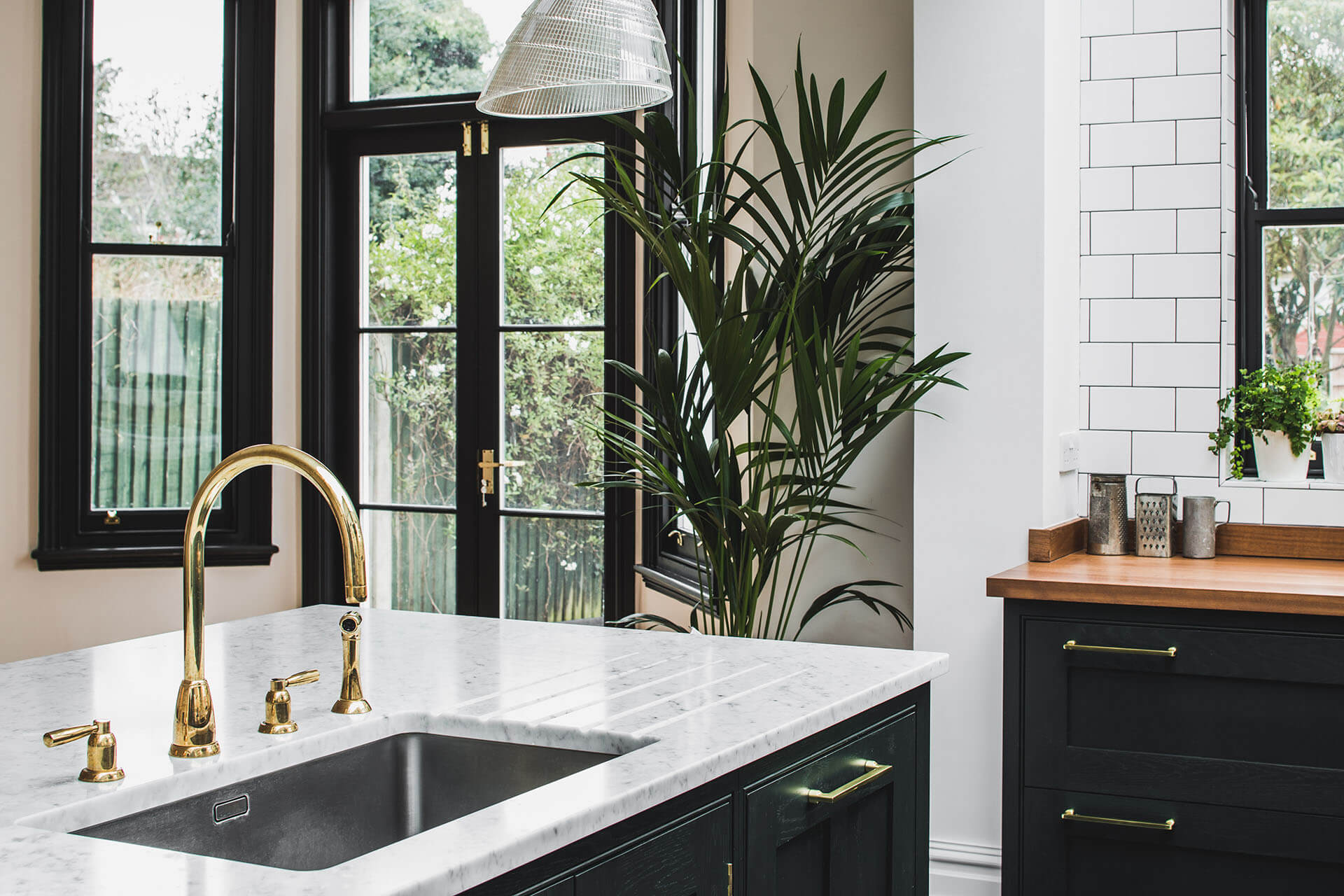 Dark Green Shaker Kitchen with sink in the island, Carrera Marble Island worktopand Perrin & Rowe Polished Brass Tap, hand painted in Little Green Obsidian Green (216)