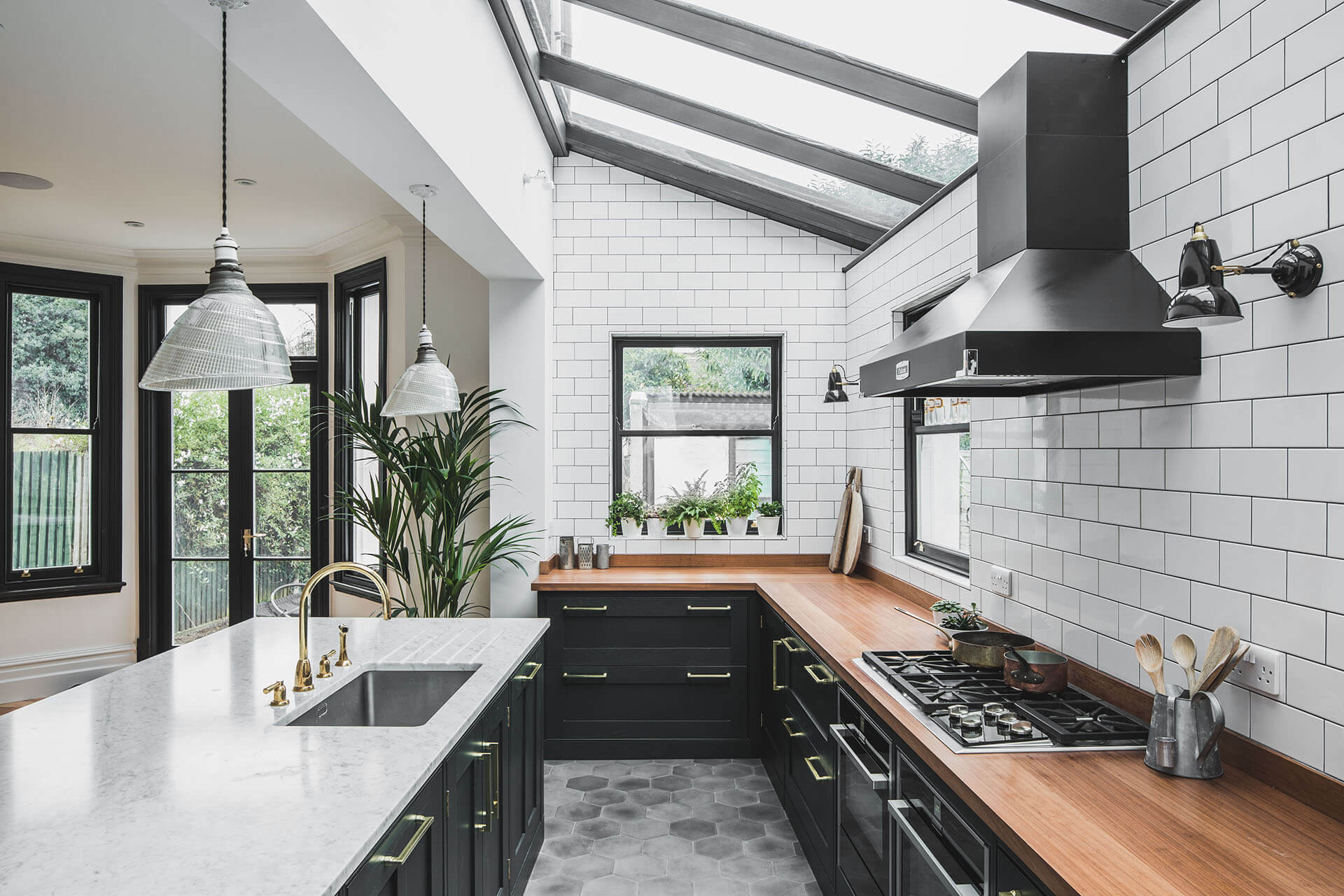 Dark Green Shaker kitchen with Island, PolishedBras Tap, Falon Hood, Wolf hob, handpainted in Obsidian Green (216) by Little Green with hexagonal concrete floor tiles