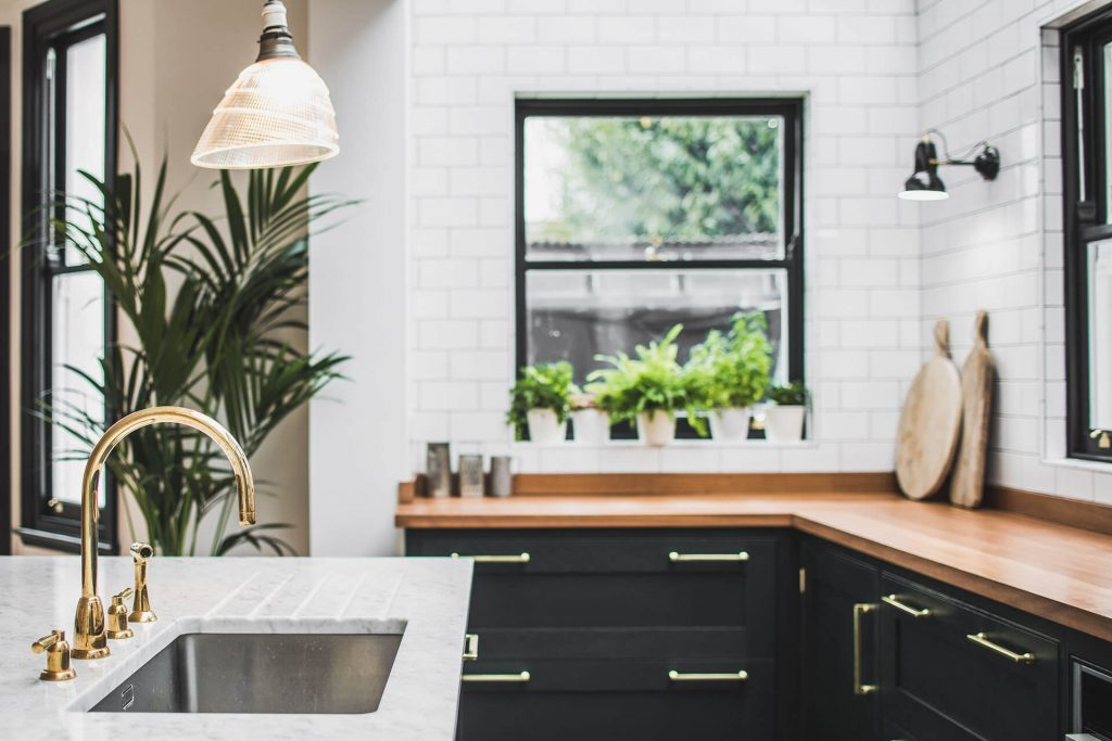 Dark Green Shaker kitchen with Polished Brass tap on a Carrera Mable island and Vintage Holophane pendant lighting