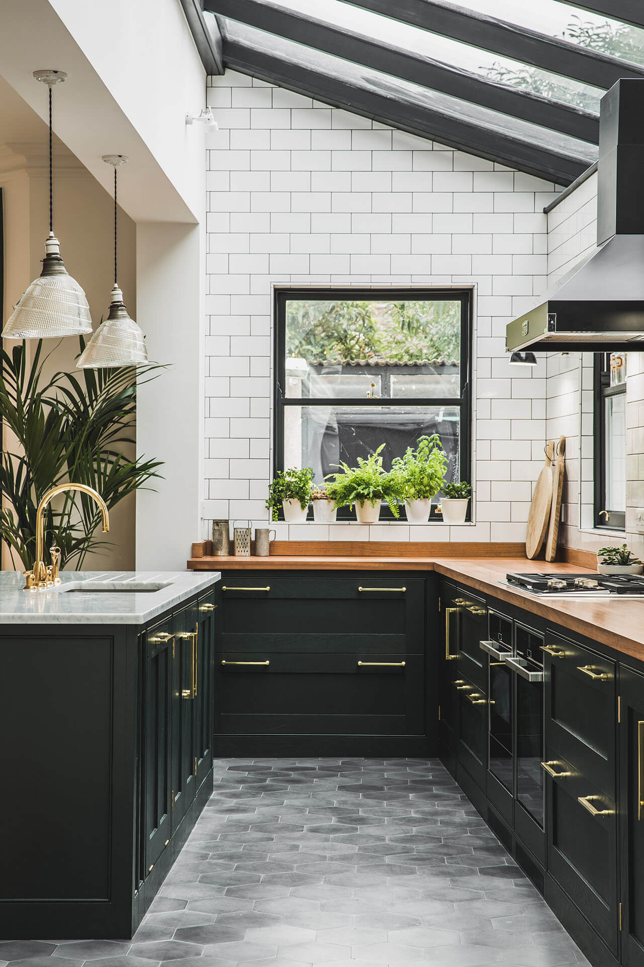 Dark Green Shaker kitchen with beading frame detaile, Iroko worktop on the perimitre and Carrera marble on the island with polished brass tap from Perrin & Rowe