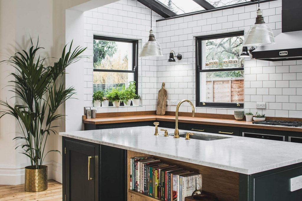 Dark Green Shaker kitchen with island incorporating open shelving for books, a Carrera Marble islandworktop and Perrin & Rowe Callisto Polished Brass tap, full wall of Metro tiles by Fired Earth