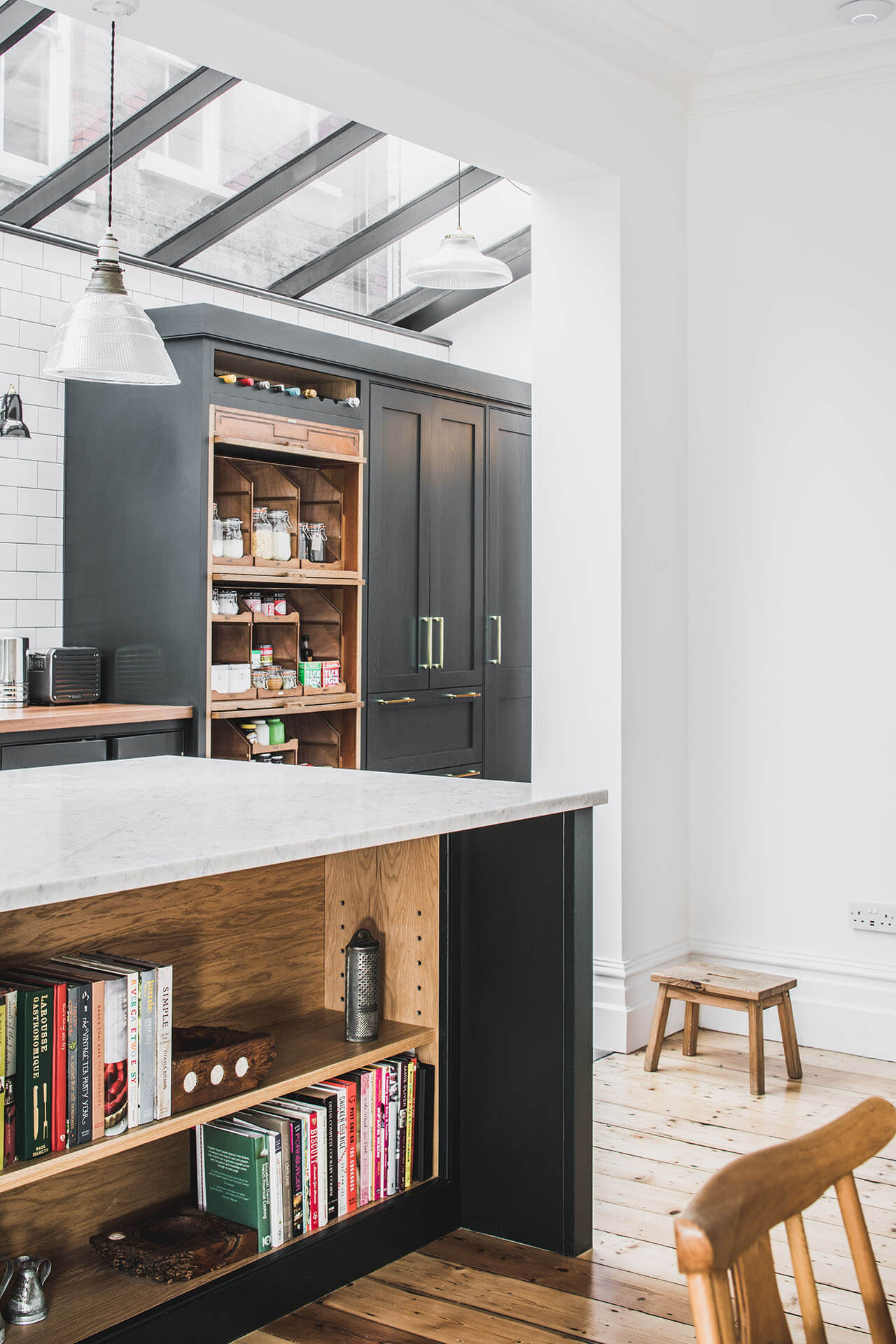 Dark Green Shaker kitchen with island with bookshelf and breakfast bar and a reclaimed vintage haberdashery cabinet