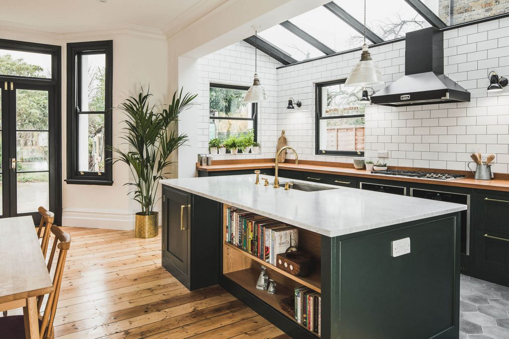 Dark Green Shaker kitchen with kitchen Island including a bookeshelf and Carrera Marble island worktop and Perrin & Rowe Calisto C Spout tap finished in Polished Brass-30