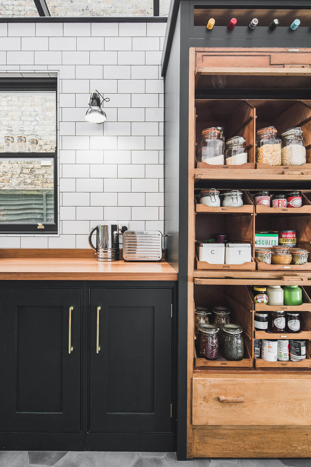 Dark Green Shaker kitchen with reclaimed vintage haberdashery cabinet fitted within the shaker cabinet run with fitted wine rack