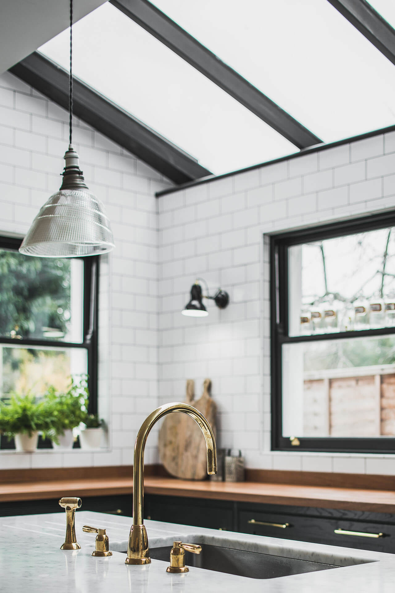 Dark Green Shaker kitchen with skylights, polished brass Perrin & Rowe tap on Carrera Marble Island