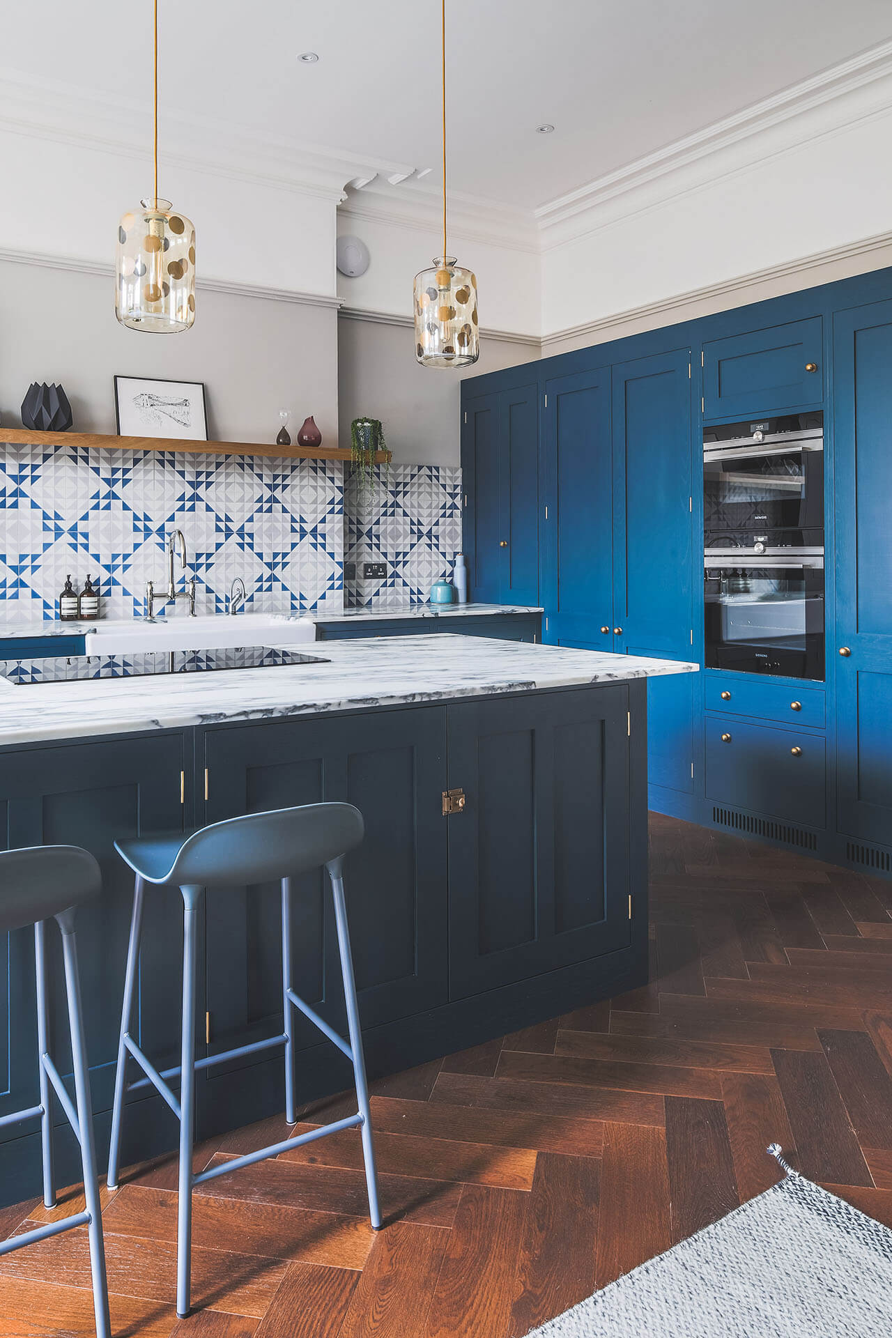 Dark blue geometric kitchen with Siemens ovens and induction hob
