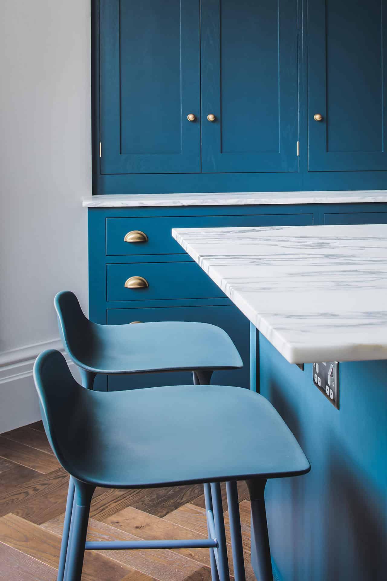 Dark blue geometric kitchen with kitchen centre island and bar stools