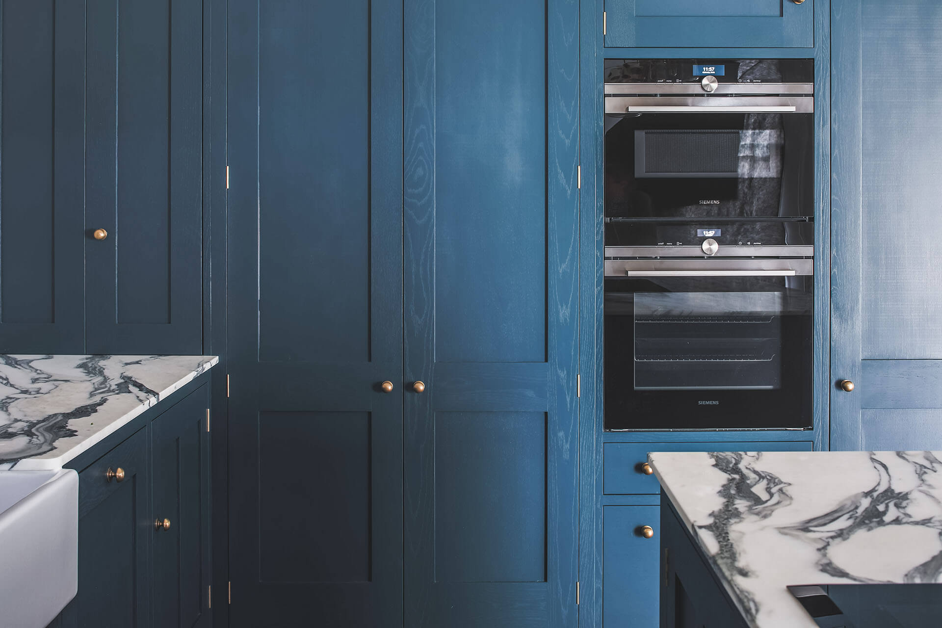 Dark blue geometric kitchen with larder cabinet and integrated eye level ovens