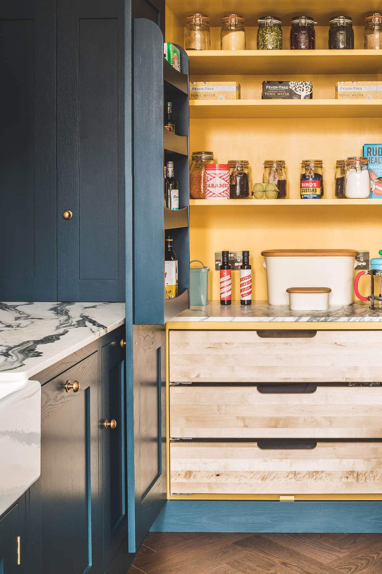 Dark blue geometric kitchen with larder cabinet and marble worktops