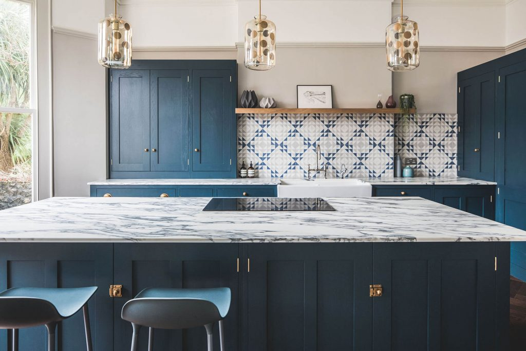 Dark blue geometric kitchen with large centre island, breakfast bar and marble worktop