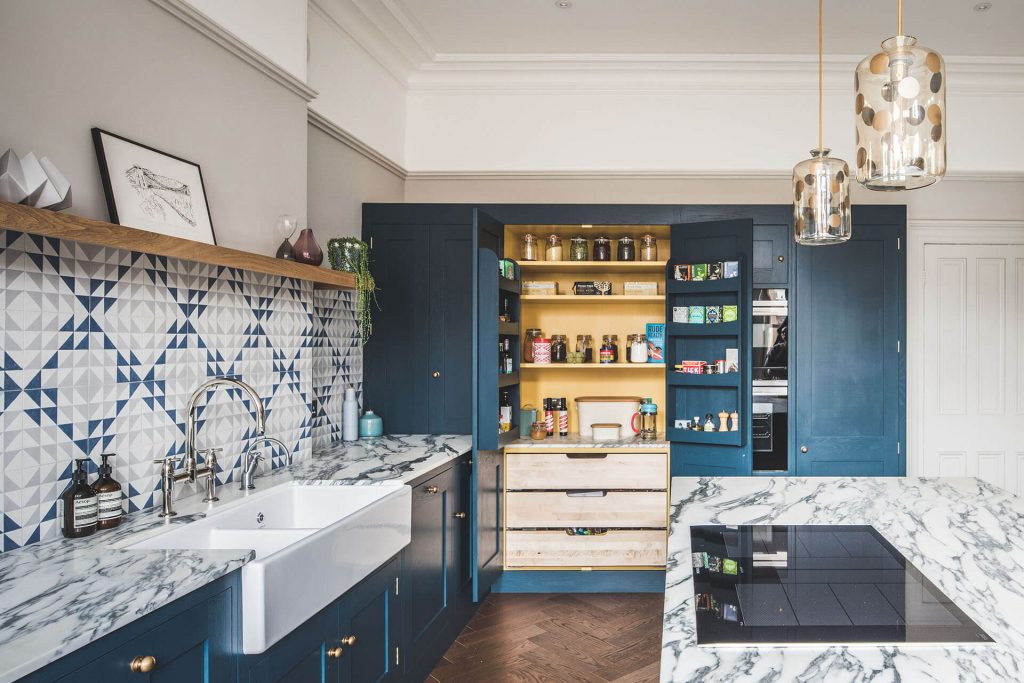Dark blue geometric kitchen with large pantry cabinet