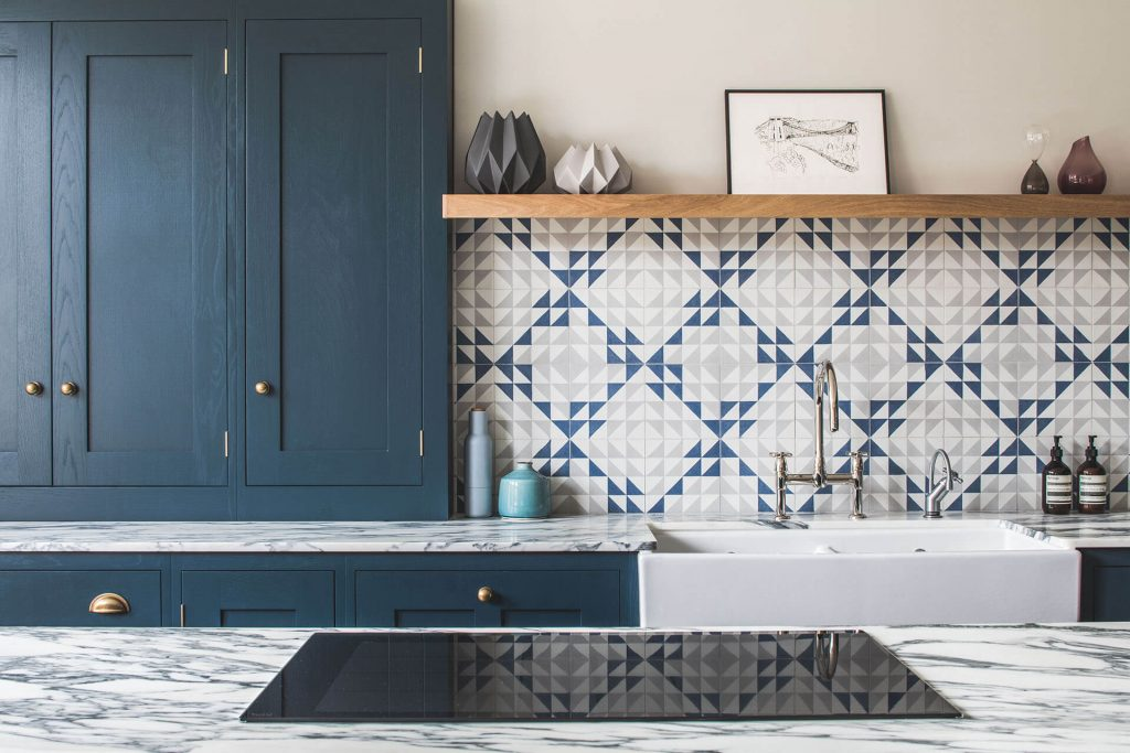 Dark blue geometric kitchen with marble worktop and induction hob