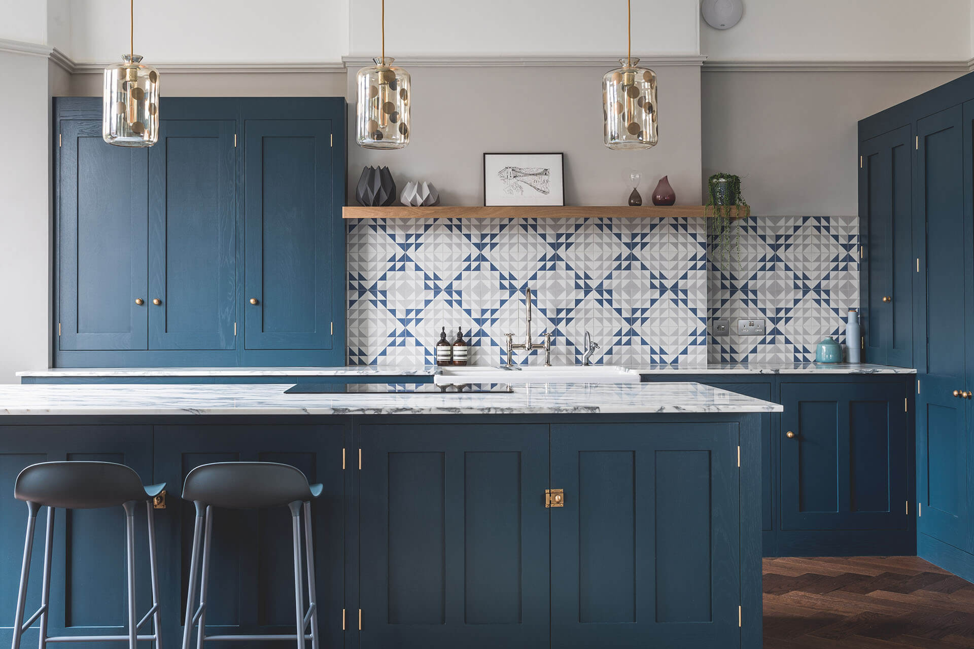 Dark blue geometric kitchen with sit on cabinet and marble worktops
